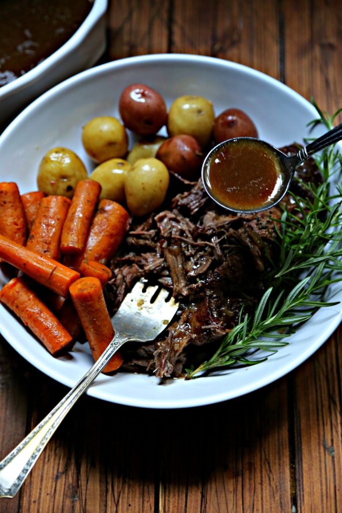 Pot roast, carrots, potatoes in white bowl with spoon of gravy.