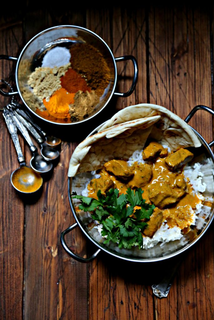 Butter chicken in silver bowl with rice. Silver bowl with spices behind.