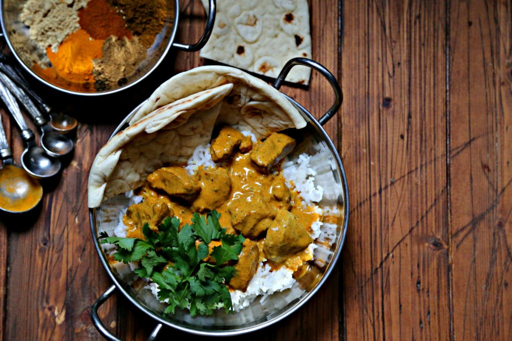butter chicken in silver bowl with rice and cilantro. Naan bread behind.