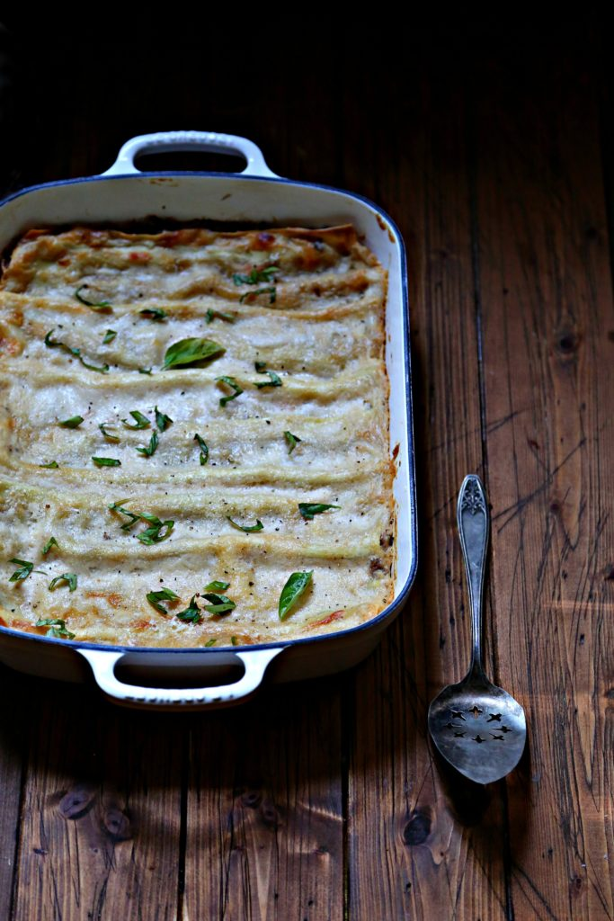 lasagna in white baking dish with serving utensil to side.