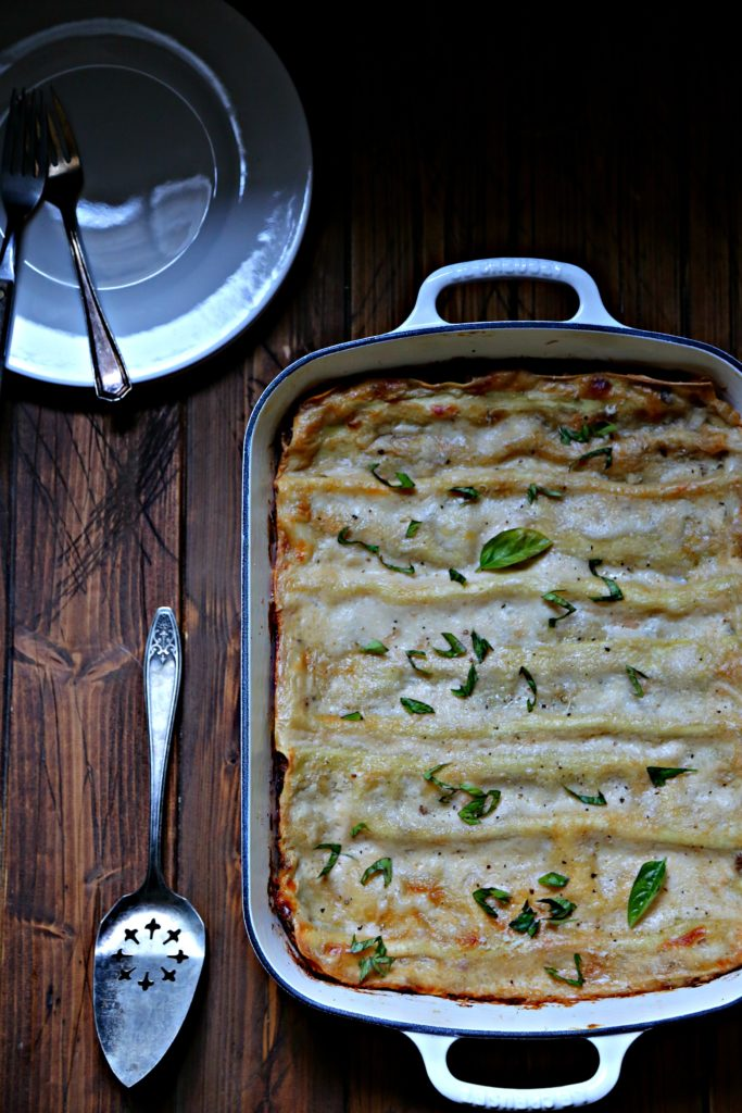 Lasagna in white baking dish. Serving utensil and plates to side.