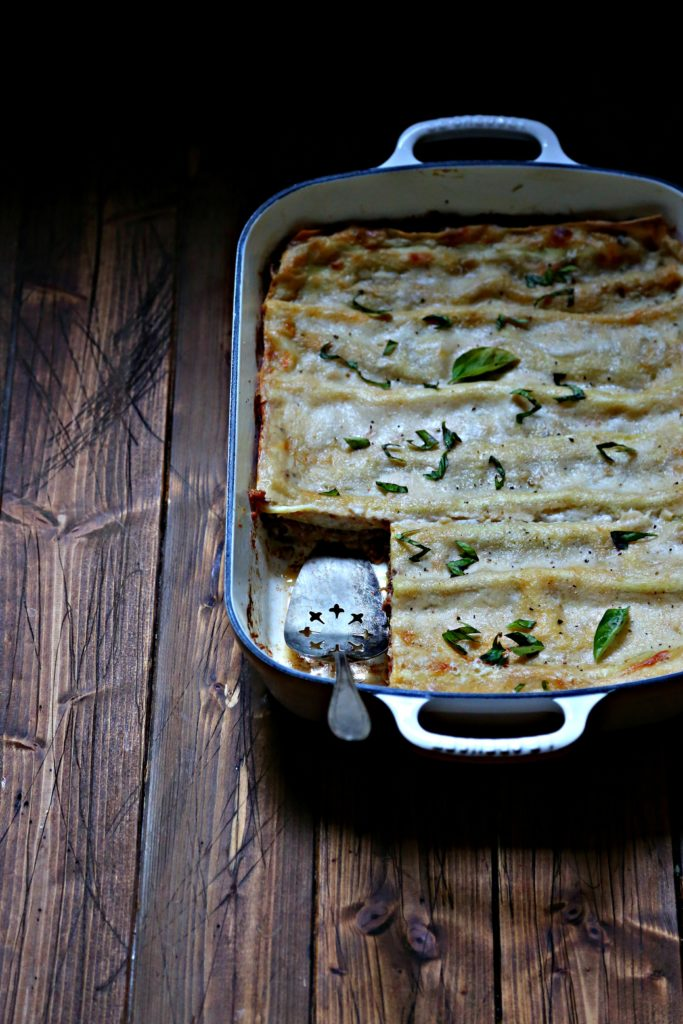 lasagna in white baking dish with serving utensil.