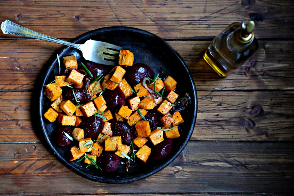 Roasted Sweet Potatoes and Beets on brown plate with fork. Glass jar of olive oil to side.