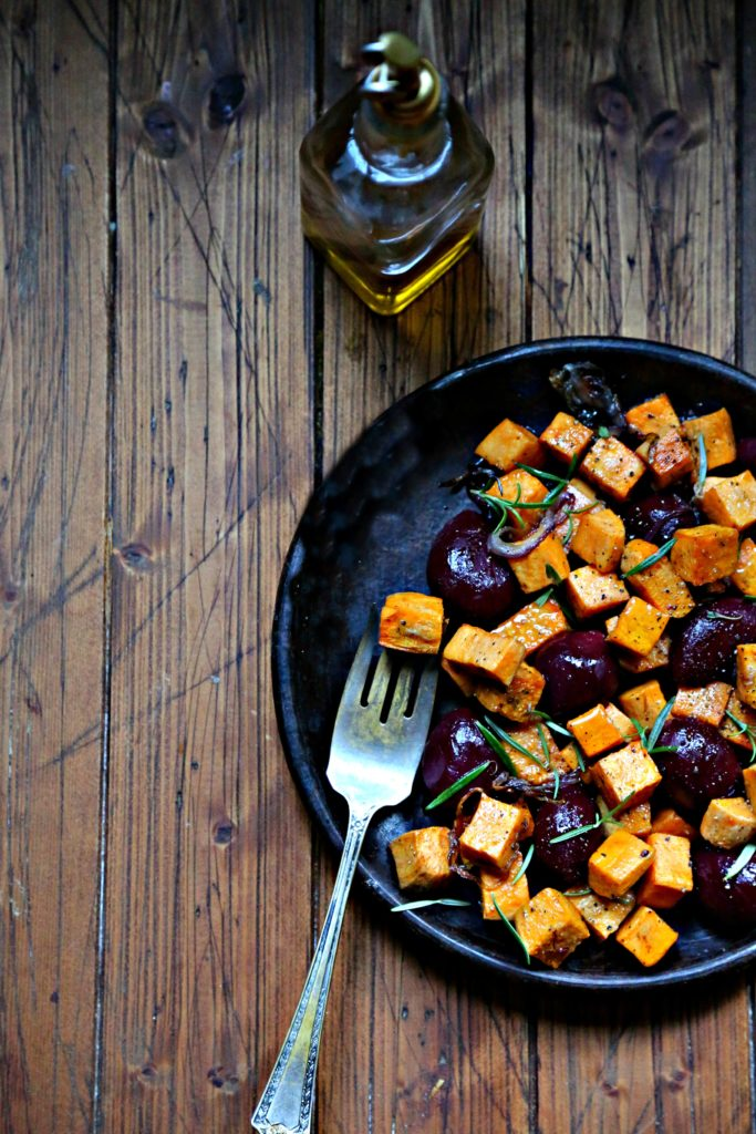 Roasted Sweet Potatoes and Beets on brown plate with fork. Glass bottle of olive oil in background.