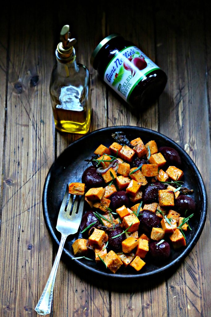 Roasted Sweet Potatoes and Beets on brown plate. Bottle of olive oil and jar of beets in background.