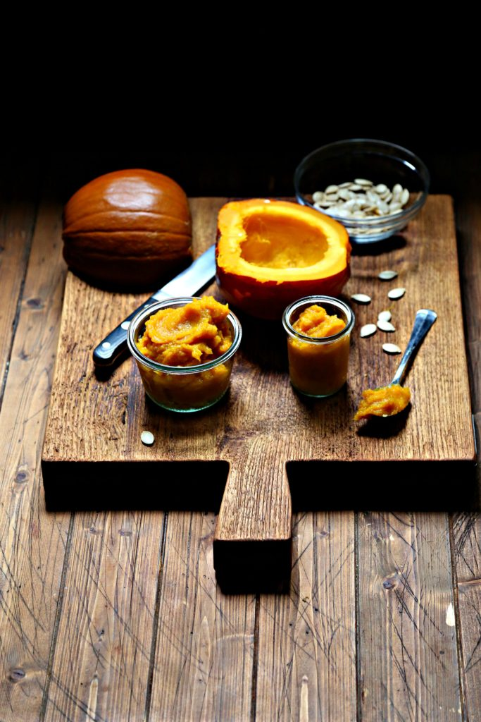 Instant Pot Pumpkin Puree in glass jars on cutting board. Cut halves of pumpkin behind with knife.