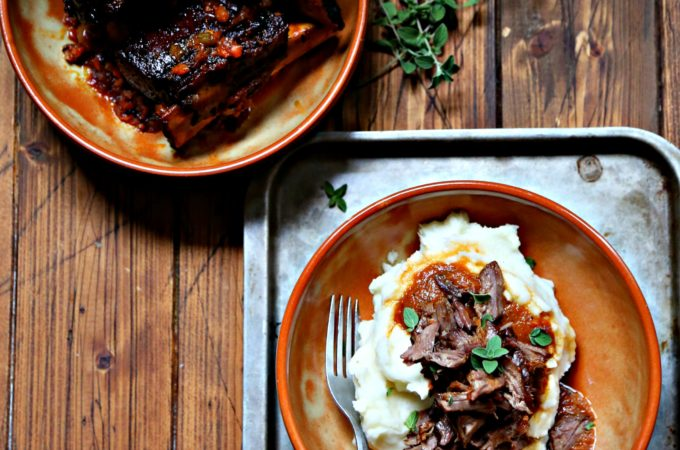 Coca Cola Braised Short Ribs in shallow brown bowl. Second bowl filled with mashed potatoes and topped with shredded ribs.