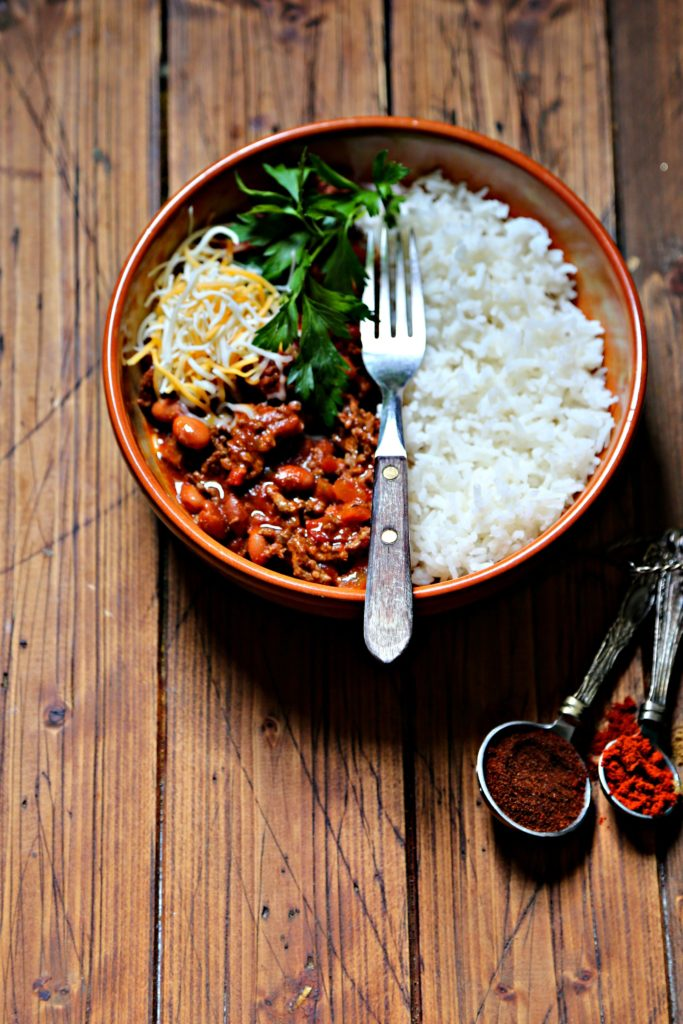 bowl of chili with rice, cheese and parsley. Measuring spoons with spices to side.