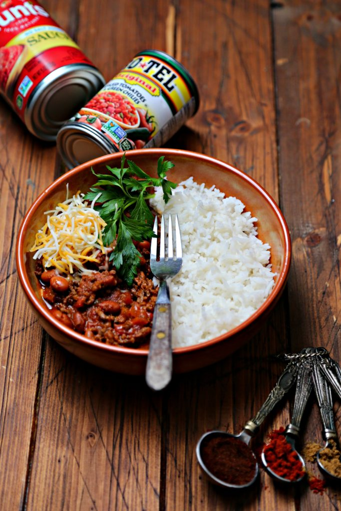 bowl of chili with rice, cheese and parsley. Cans of tomatoes in background.
