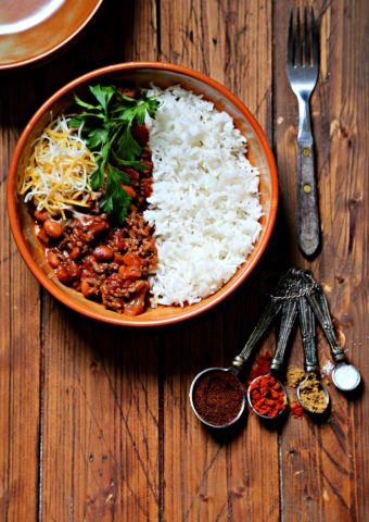 bowl of chili with rice, cheese and parsley. Fork and measuring spoons with spices to side.