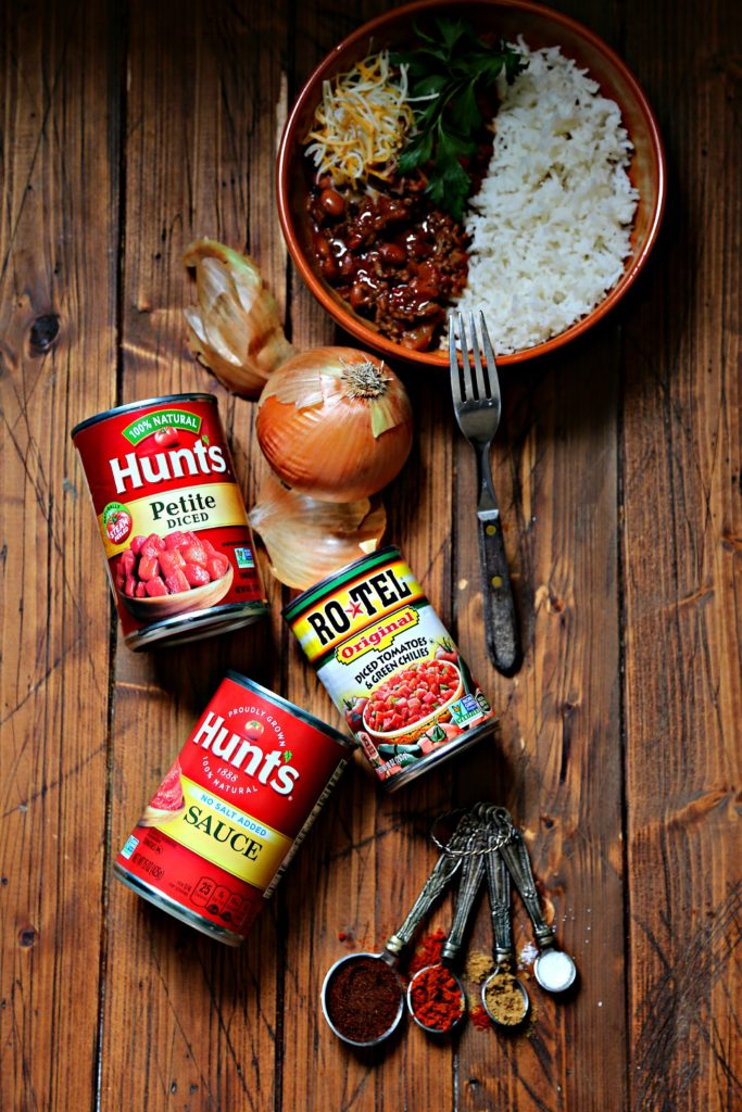 bowl of chili with rice. Cans of tomatoes, onion and measuring spoon with spices in front.