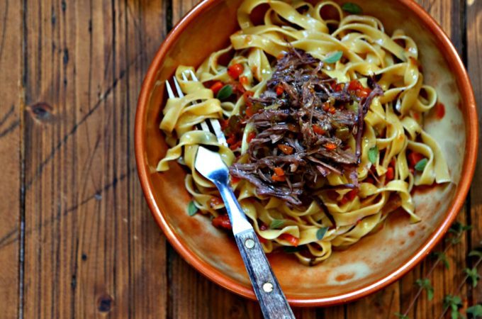 Bowl of pasta with shredded short ribs. Dried pasta nests in background.