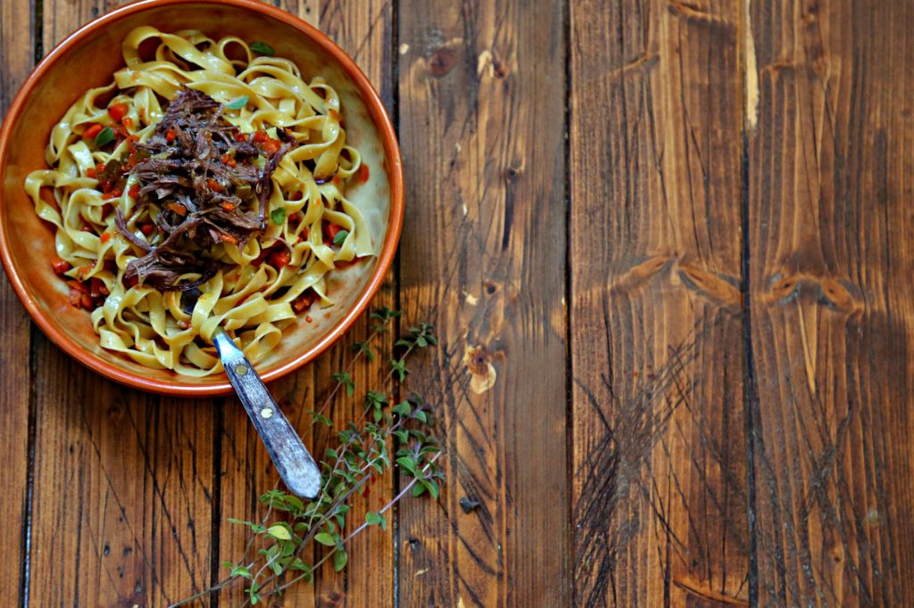 brown bowl with pasta and shredded short ribs.