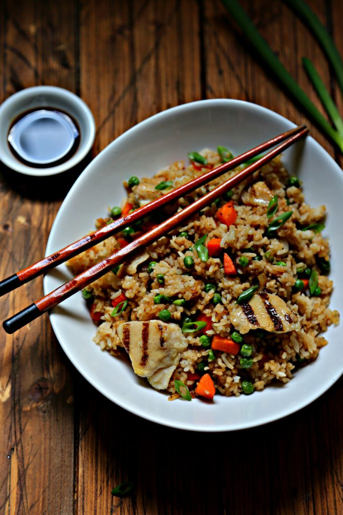 chicken fried rice in white bowl with chopsticks.