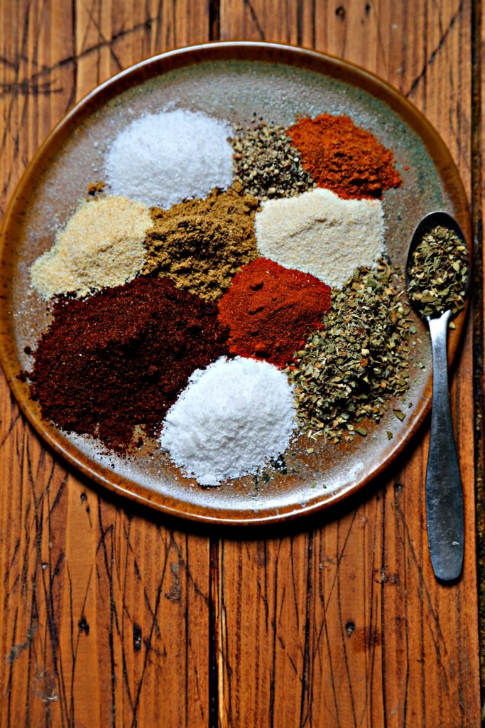 Spices to make fajita seasoning on brown plate with spoon.