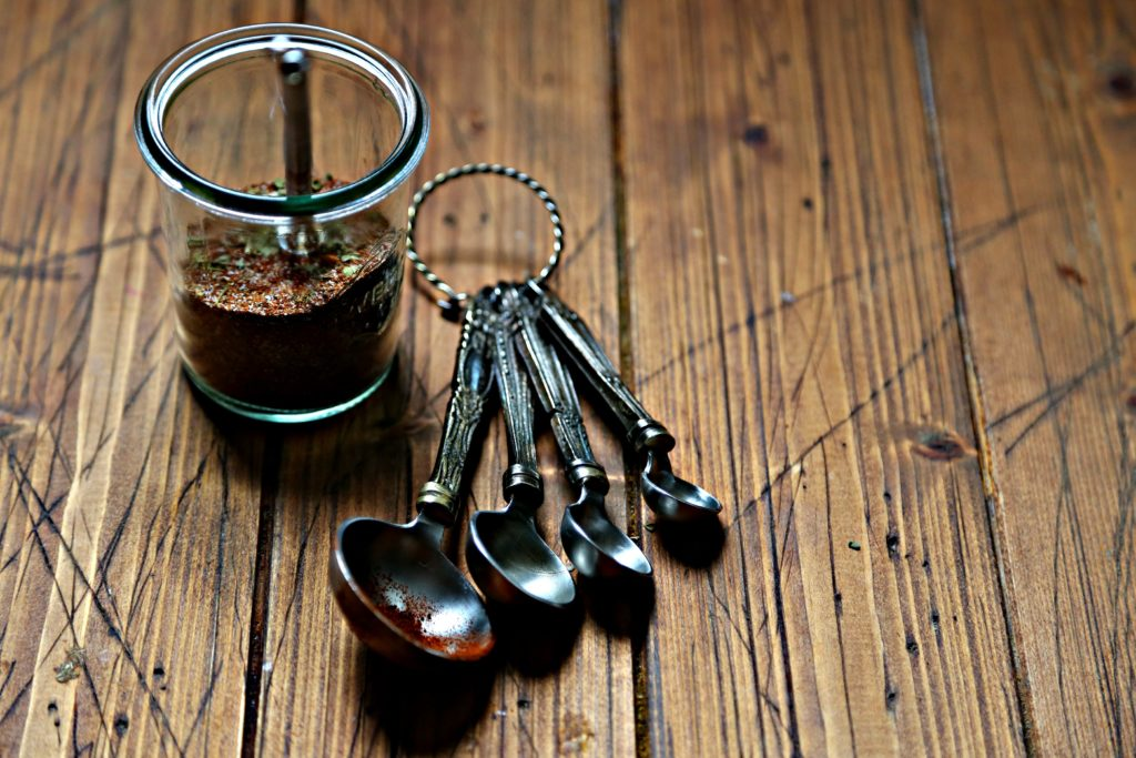 Small glass jar of fajita seasoning with whisk.