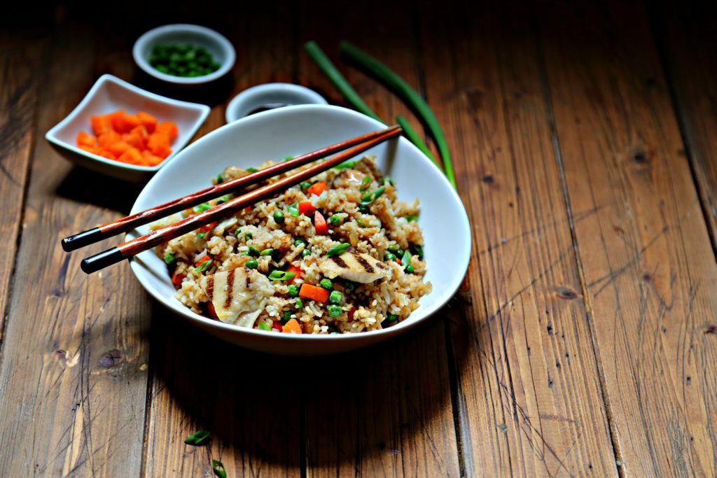 Chicken fried rice in white bowl with chopsticks. Small bowl of ingredients in background.