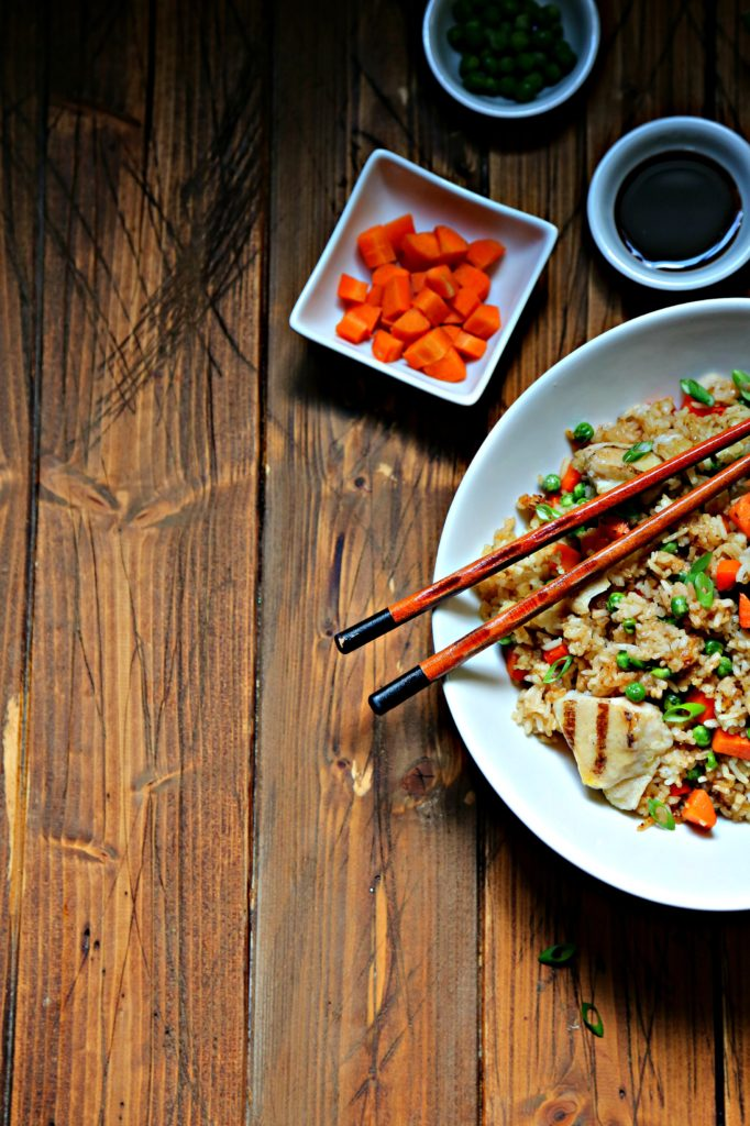 Chicken Fried Rice in white bowl. Small bowl of carrots to side.