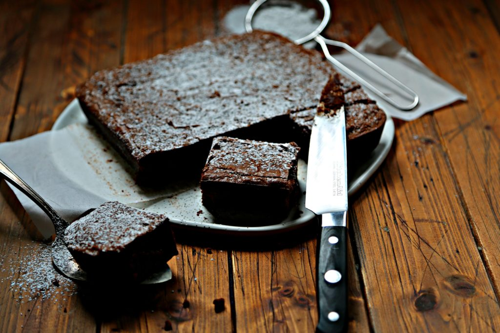 sweet potato brownies on white plate with knife.