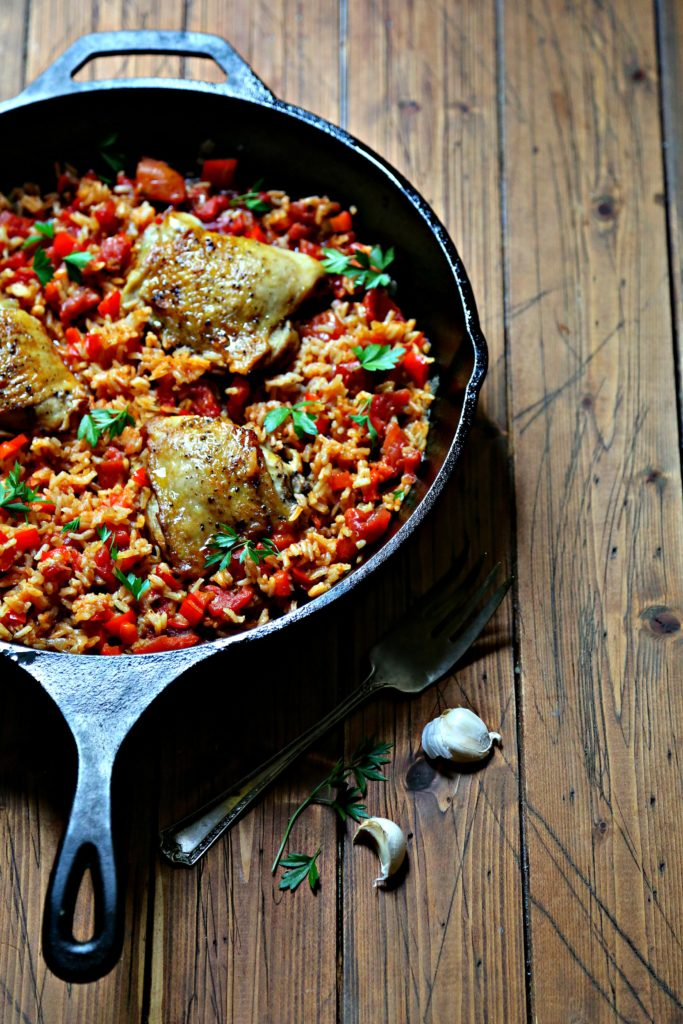cast iron skillet with arroz con pollo, chicken and rice