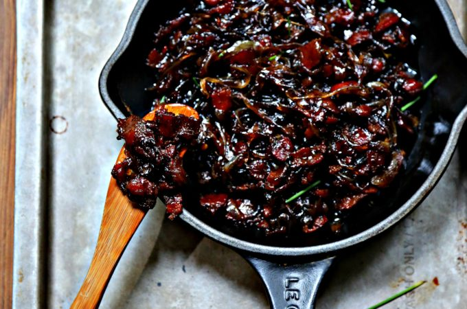 bacon jam in small black skillet on baking sheet. Wooden knife with jam to left.