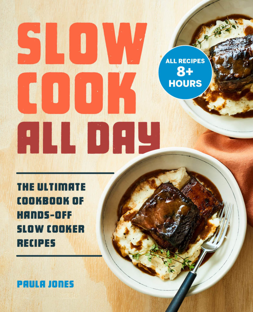 cookbook cover. Text reads slow cook all day the ultimate cookbook of hands off slow cooked recipes paula jones. Bowl of mashed potatoes with short rib and gravy with fork. Additional bowl of mashed potatoes and short rib in background.