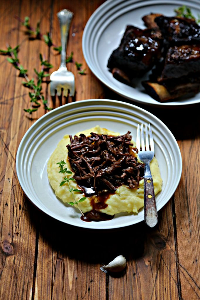 White bowl with mashed potatoes, shredded short rib and gravy and fork. Serving fork to side. White bowl with short ribs in background.
