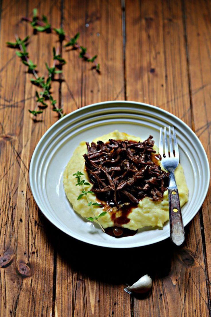 mashed potatoes, shredded short ribs and gravy in white bowl with fork. Fresh thyme in background.