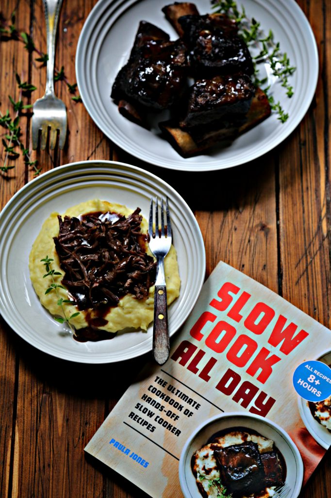 mashed potatoes shredded short ribs with gravy and fork in white bowl. White bowl with short ribs in background. Cookbook in front. Serving fork to side.