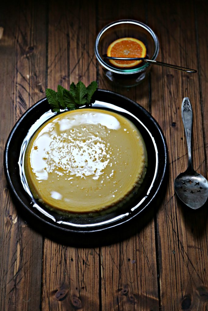 flan garnished with mint on brown plate. Small glass bowl with metal sieve and half orange in background. Serving utensil to right of plate.