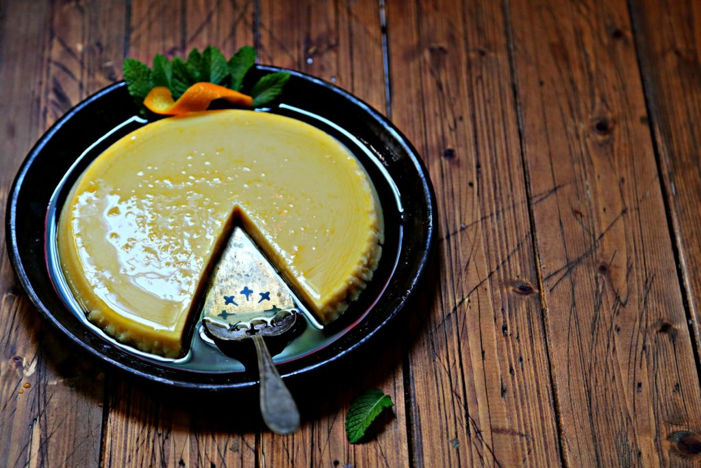 flan garnished with mint and orange peel on brown plate. Slice missing, pie serving utensil in it's place.