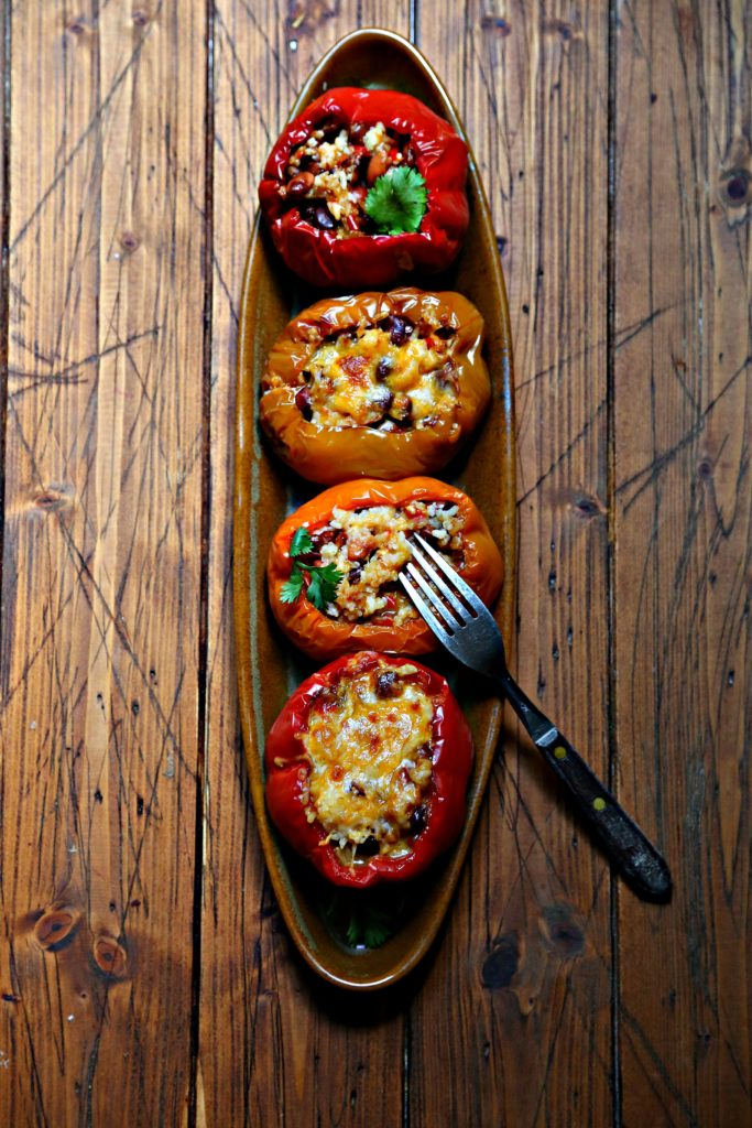 4 rice stuffed bell peppers on brown oblong tray. Fork sitting on one pepper.