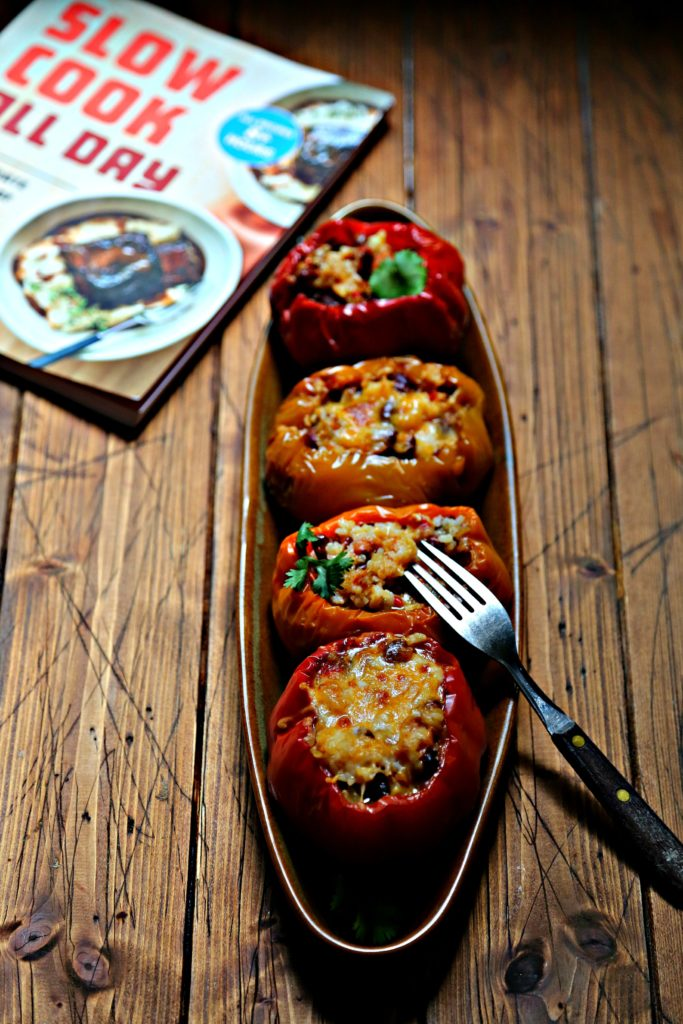 4 rice stuffed bell peppers on brown oblong tray. Fork piercing into one pepper. Slow cooker cookbook in background.