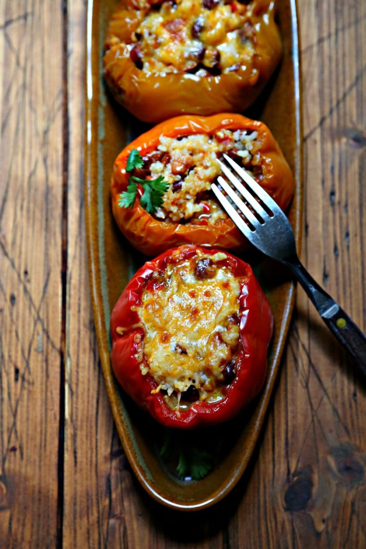 close up of 3 stuffed bell peppers on brown oblong tray. Fork poking into middle bell pepper.