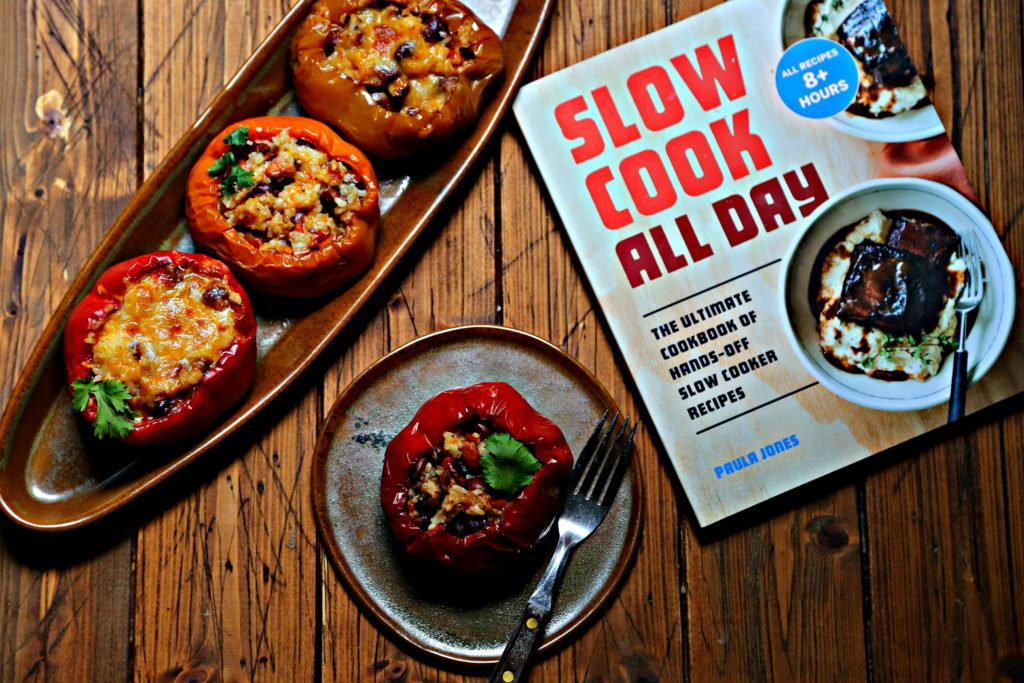 3 stuffed bell peppers on brown oblong tray. Circular plate with one stuffed pepper and fork in front. Slow cooker cookbook to side.
