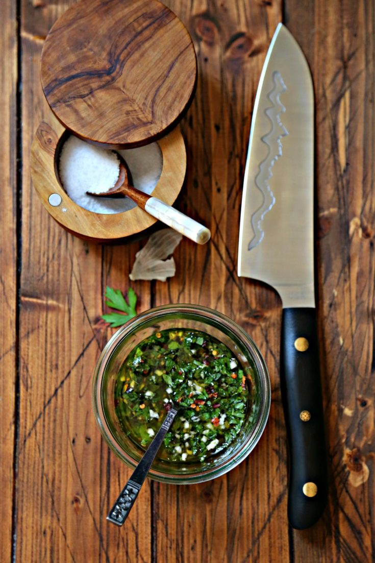 glass jar with chimichurri sauce and spoon. Salt cellar with spoon behind. Knife with black handle to side.