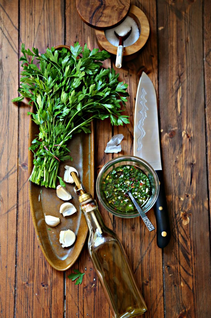 brown oblong tray with bunch of parsley, garlic cloves, jar of olive oil partially laying on tray. Glass jar of chimichurri with spoon, knife with black handle to right. Salt cellar with spoon in background.