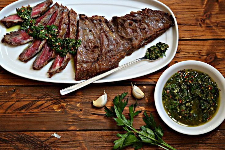 flank steak partially sliced with chimichurri sauce on white plate with fork. Bowl of chimichurri, cloves of garlic and parsley to side.