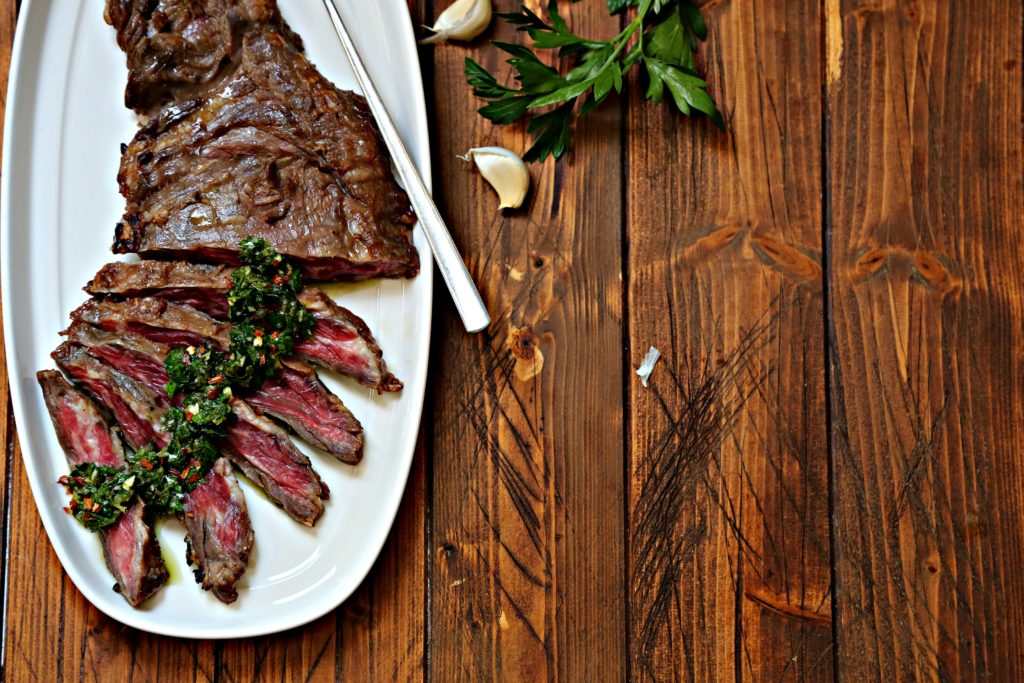 Flank steak that is partially sliced with chimichurri sauce drizzled on top sitting on white tray with spoon. Garlic cloves and parsley to right.