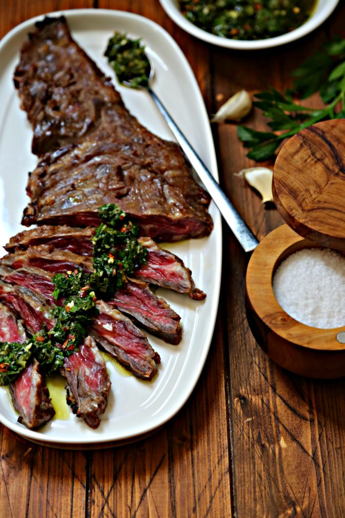 Flank Steak partially sliced with chimichurri drizzled on top on white oblong tray. Salt cellar, garlic cloves and fresh parsley to side.