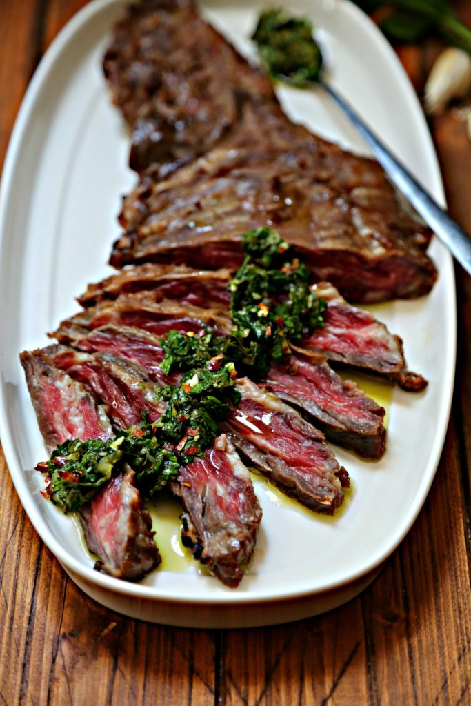 Flank steak on white oblong tray. Partially sliced with chimichurri sauce drizzled on top. Spoon with chimichurri resting on tray.
