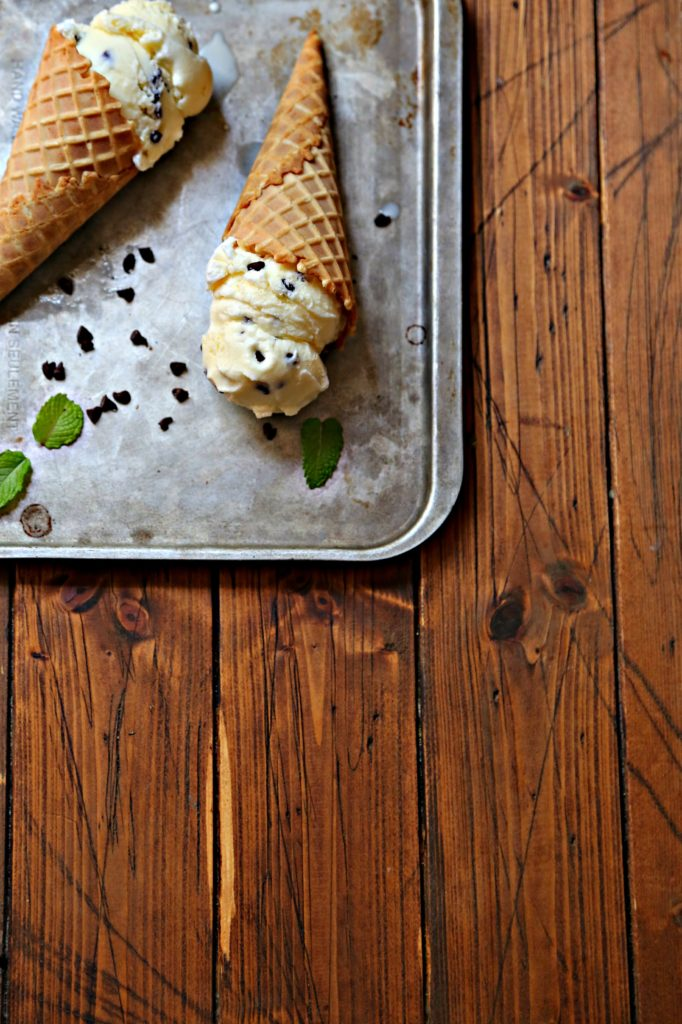 2 mint chocolate chip ice cream cones laying on baking sheet with scattered chocolate chips and mint leaves.