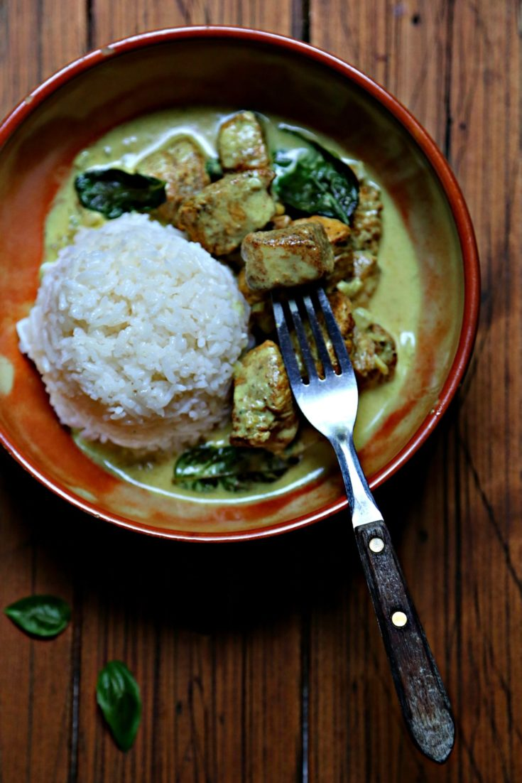Brown bowl with rice ball, and thai basil curry chicken. Fork in piece of chicken.