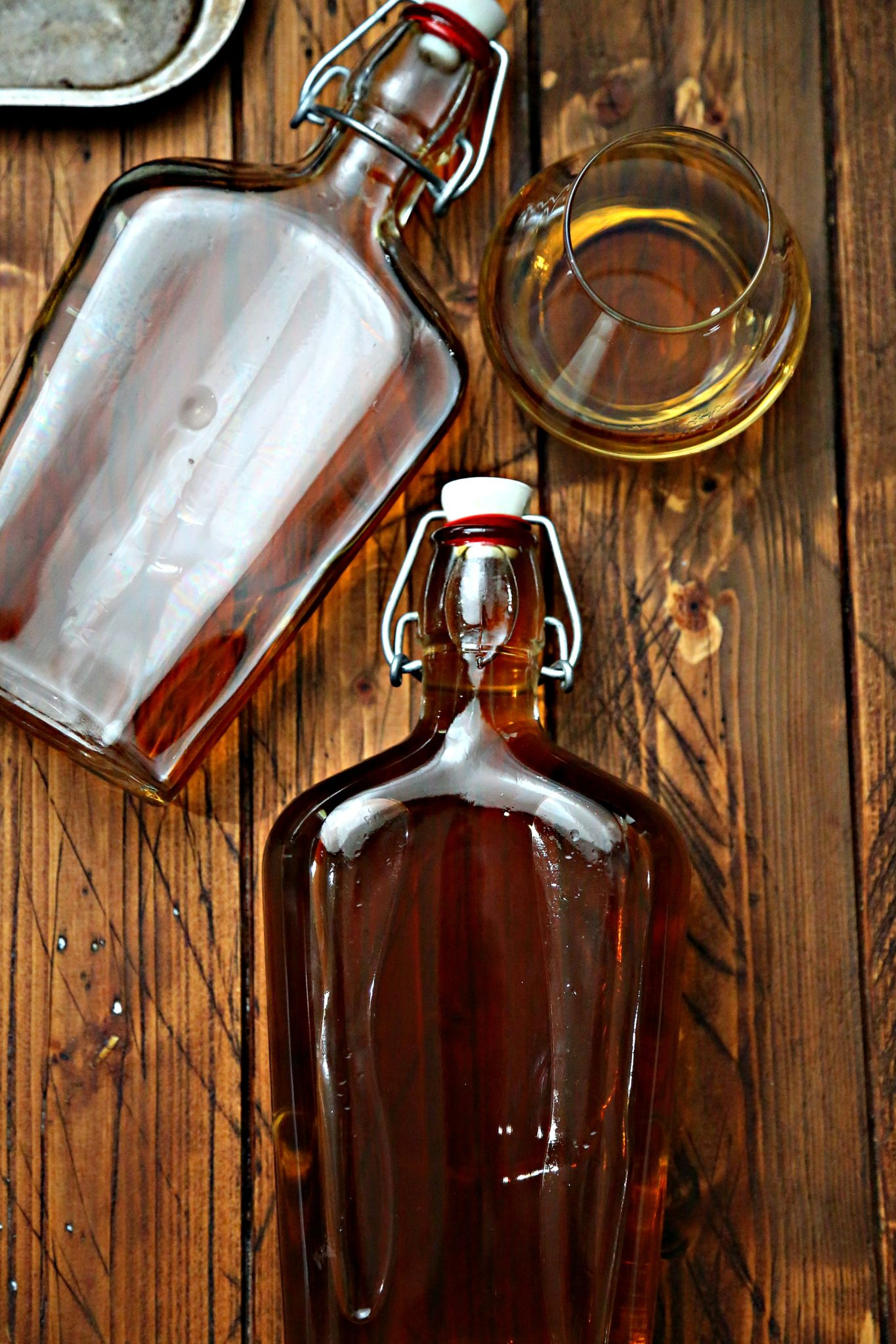 Glass Bottle with stopper of homemade amaretto with small white bowl of brown sugar in background via Bell'Alimento