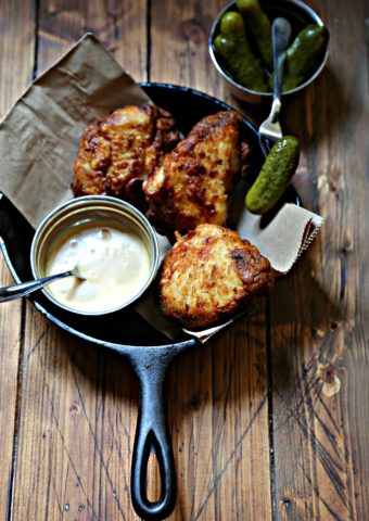 cast iron skillet with fried chicken and sauce in metal bowl with spoon. Pickles behind.