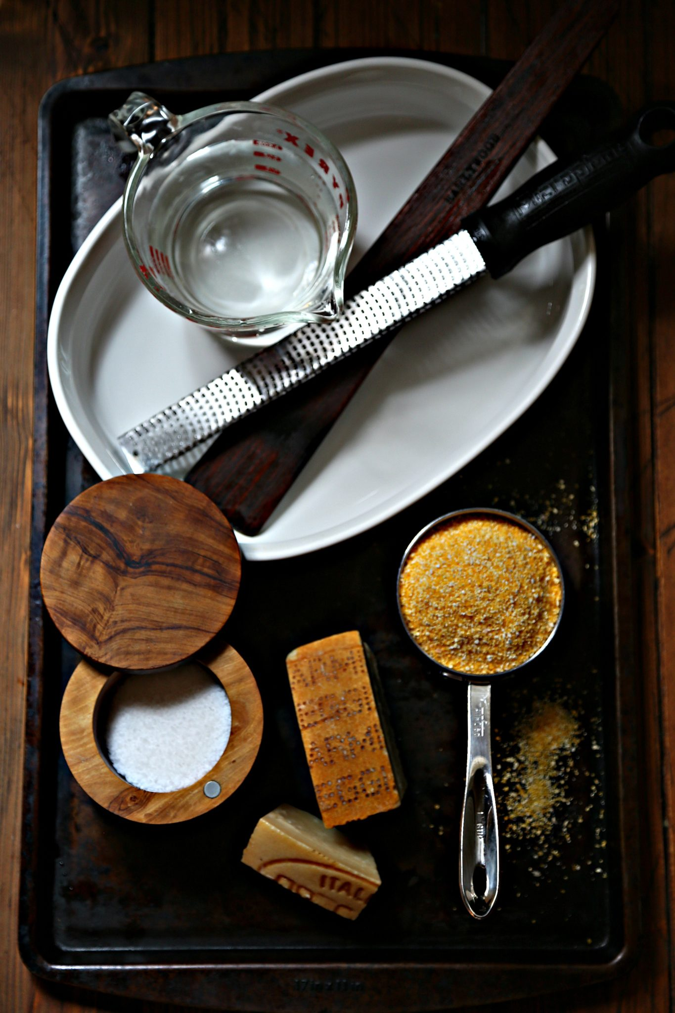 polenta cakes ingredients and tools wood background via bell'alimento