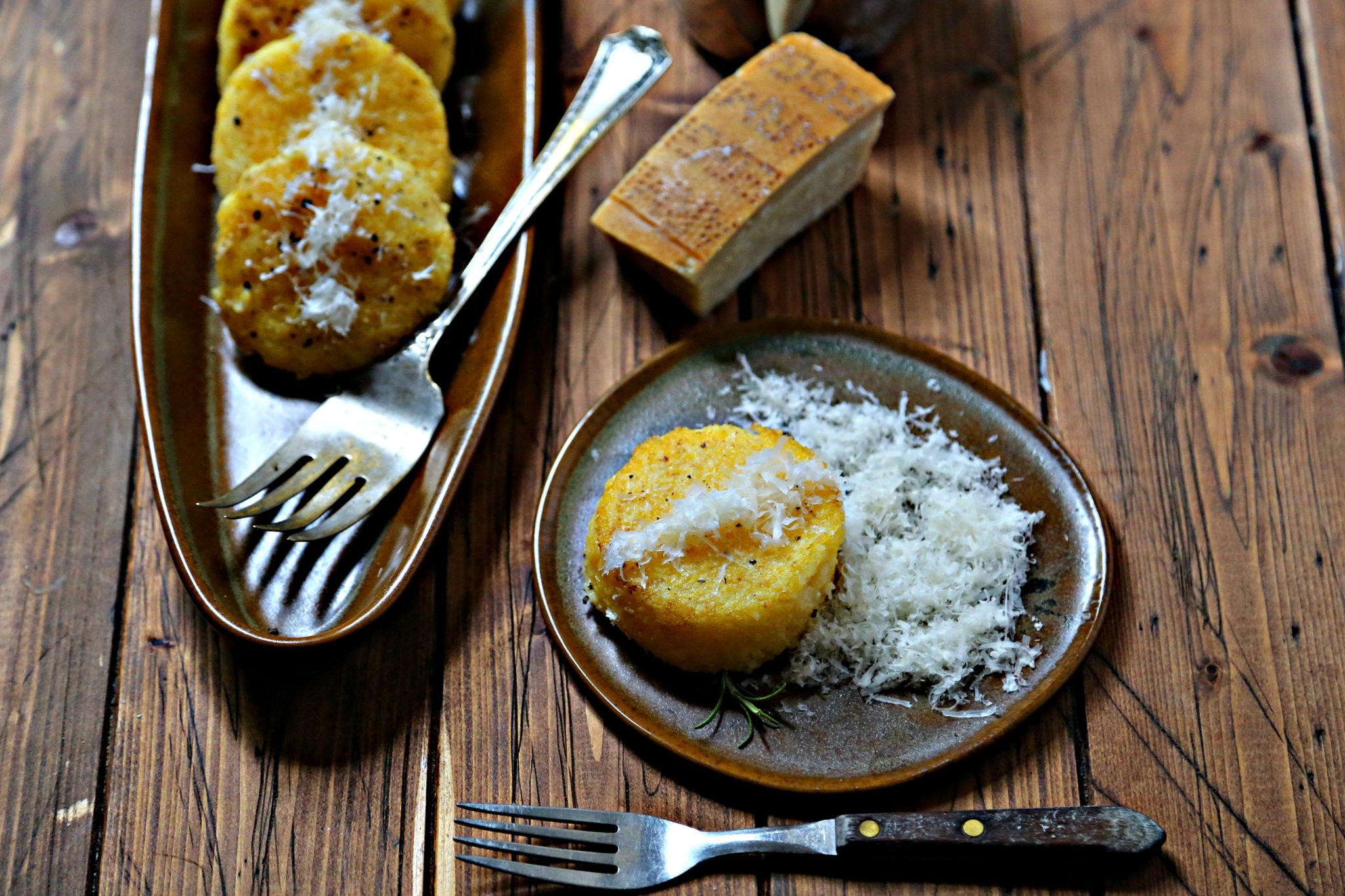 Polenta Cakes on brown platter with cheese and wood background via bell'alimento