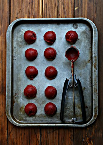 11 scoops of tomato paste on baking sheet with cookie scoop.