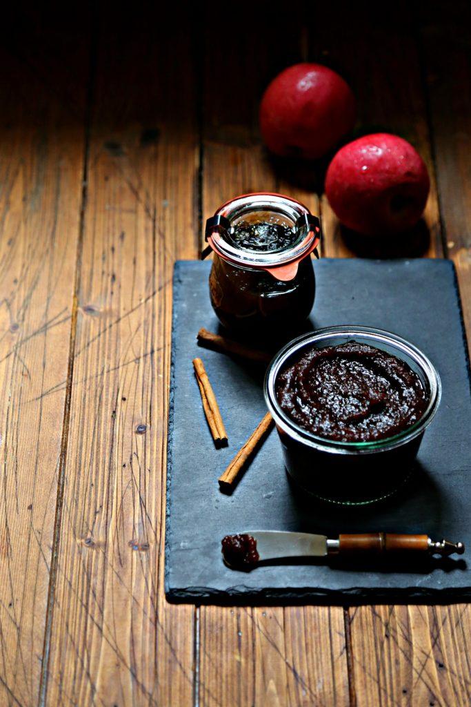 glass jars of apple butter on black slate. Apples and cinnamon sticks around jars.