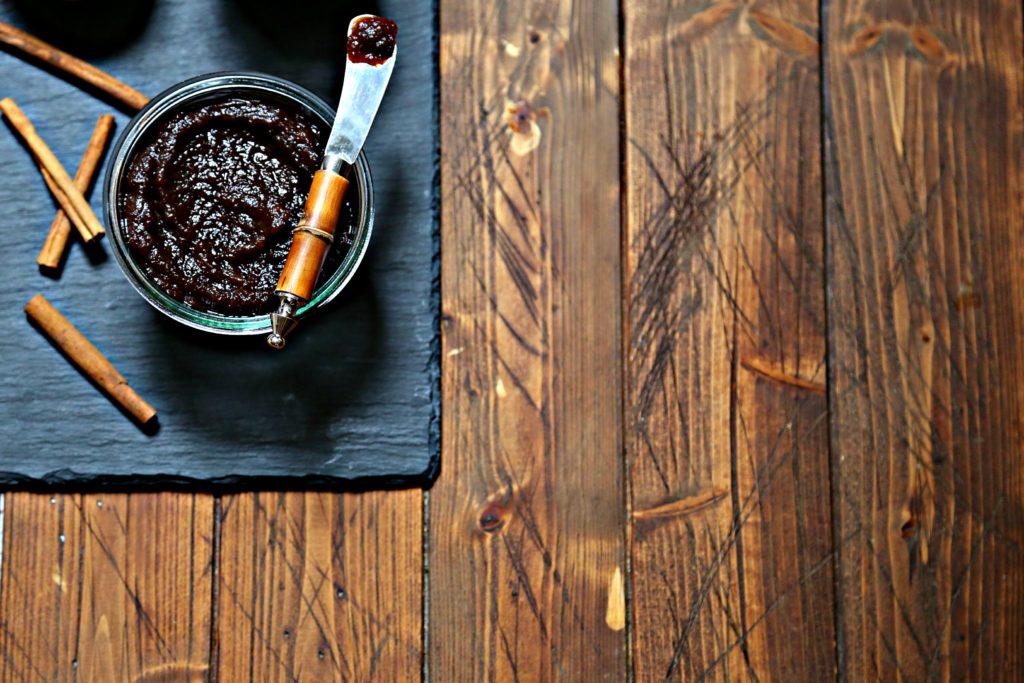 jar of apple butter with spreader on black slate.